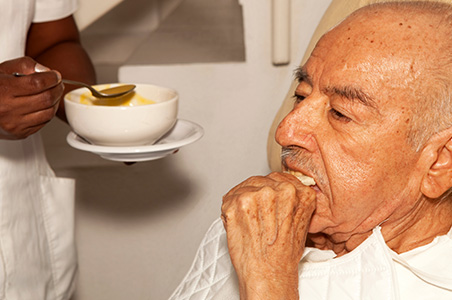 Elderly man being assisted with eating