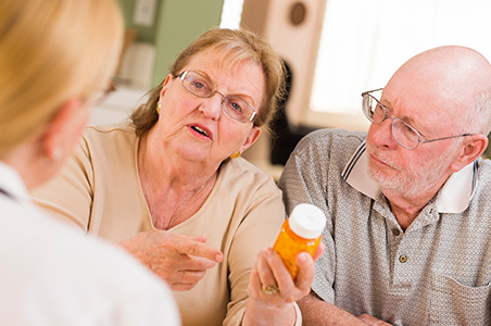 A male and female discussing medication with clinician